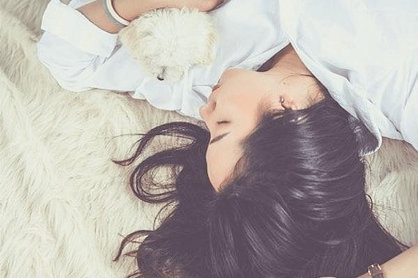 Frau schläft mit Teddybär ein